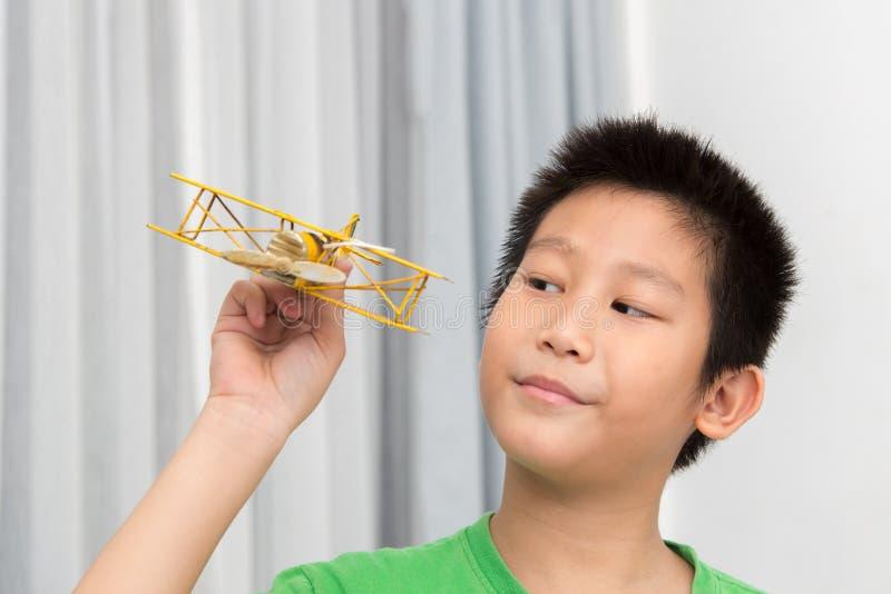 Asiatischer Junge, der gelbe Weinlesefläche spielt lizenzfreies stockbild