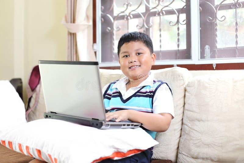 Asiatischer Junge, der Notizbuch spielt stockbild