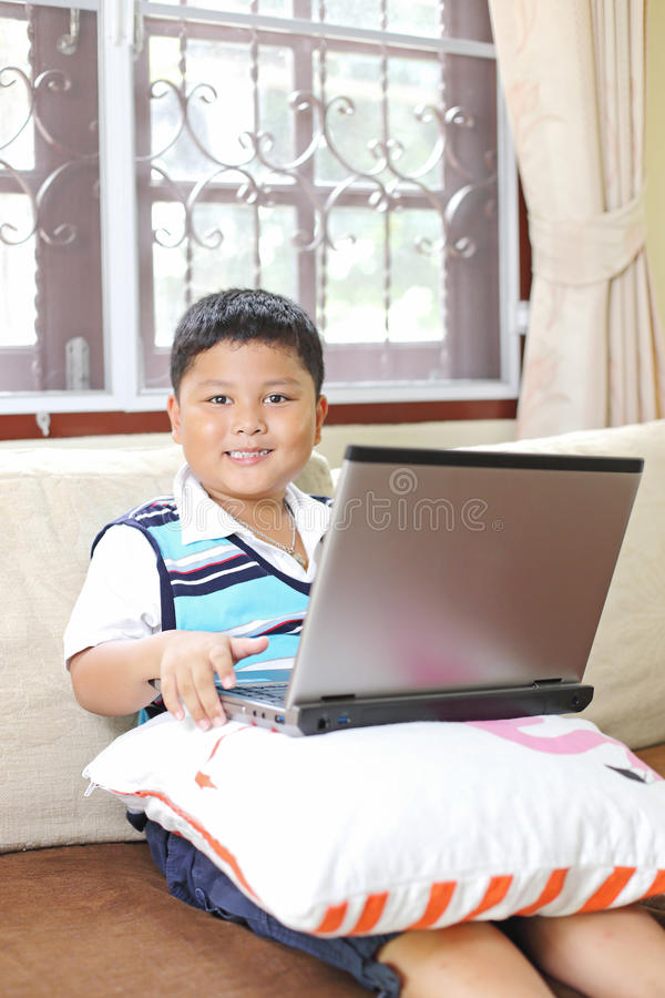 Asiatischer Junge, der Notizbuch spielt stockfotografie