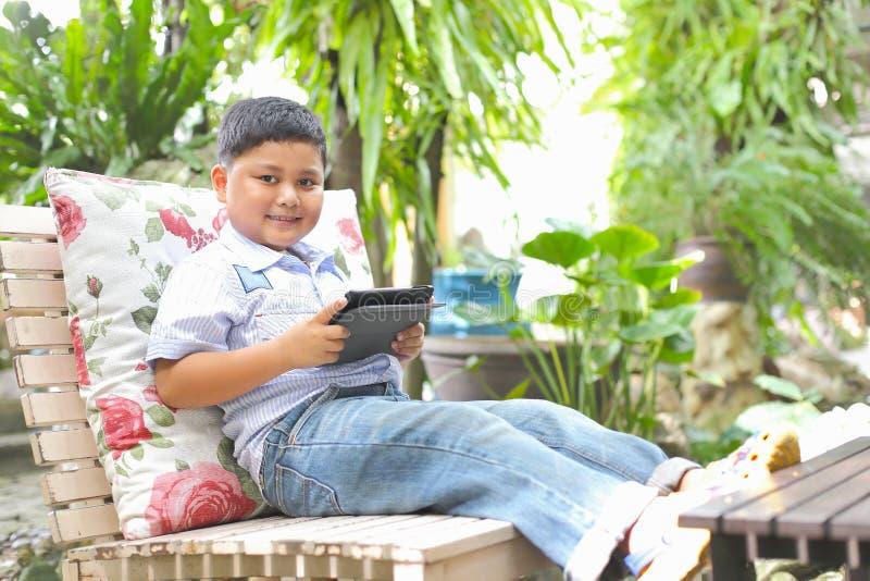 Asiatischer Junge, der Tablette spielt lizenzfreie stockbilder