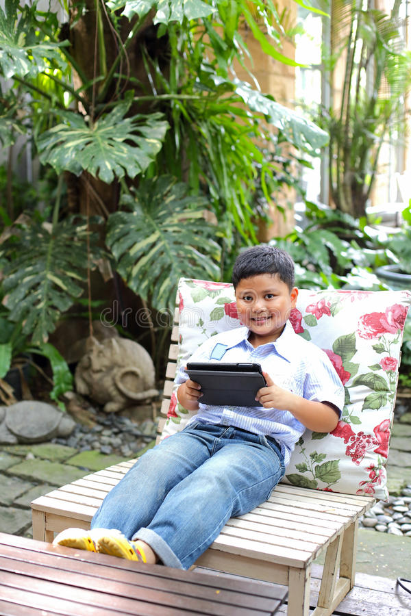 Asiatischer Junge, der Tablette spielt stockbilder