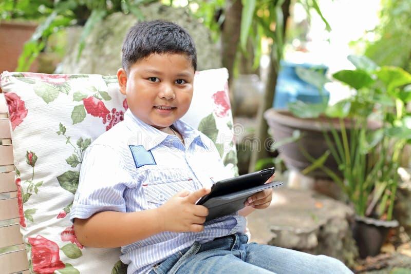 Asiatischer Junge, der Tablette spielt stockfotografie