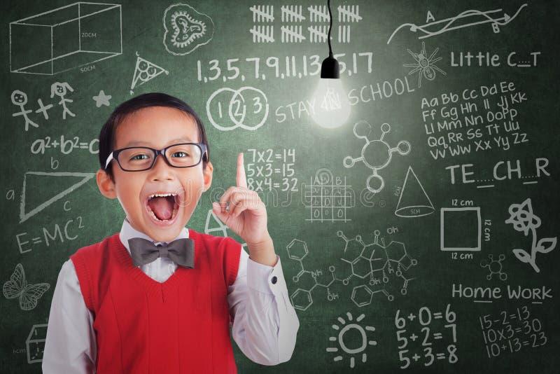 Asiatischer Junge hat Idee unter gebeleuchteter Birne im Klassenzimmer lizenzfreie stockfotos