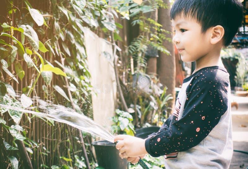 Asiatischer Junge ist Bewässerungsanlage im Garten lizenzfreie stockfotos