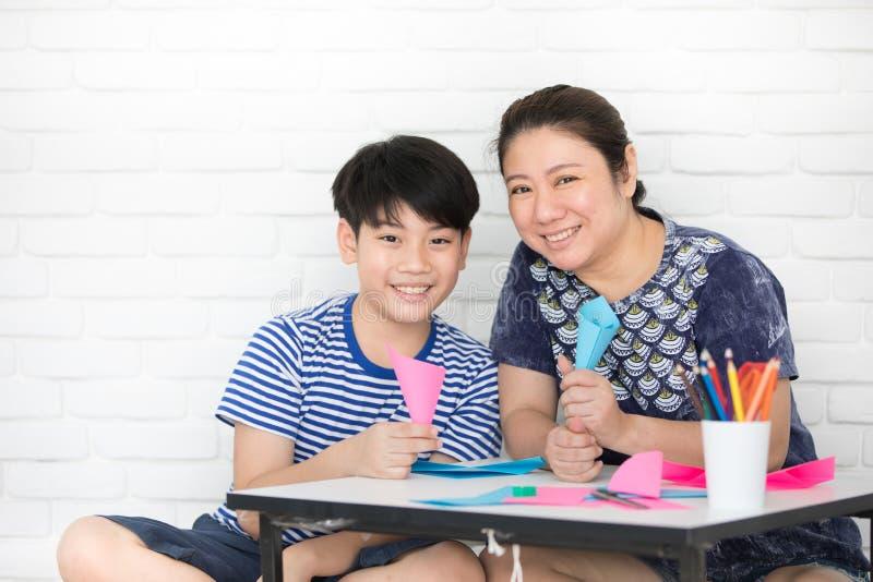 Asiatischer Junge mit der Mutter, die zu Hause Ihre Hausarbeit unterrichtet und lernt stockbild