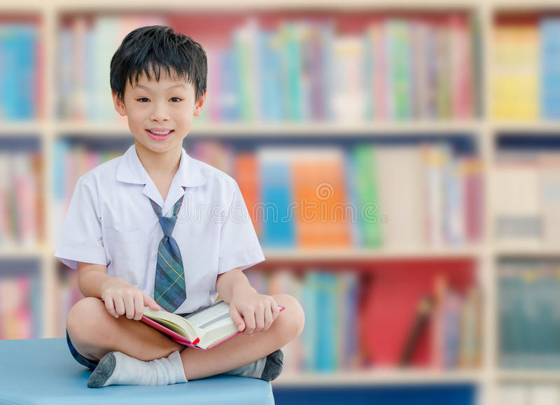 Asiatischer Jungenstudent in der Schulbibliothek lizenzfreie stockfotografie