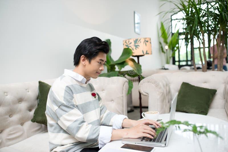 Asiatischer junger Geschäftsmann, der mit Laptop am Stadtcafé arbeitet lizenzfreie stockfotografie
