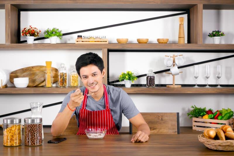 Asiatischer junger Mann, der Getreide mit Milch auf Holztisch zum Frühstück zu Hause morgens isst lizenzfreie stockfotos