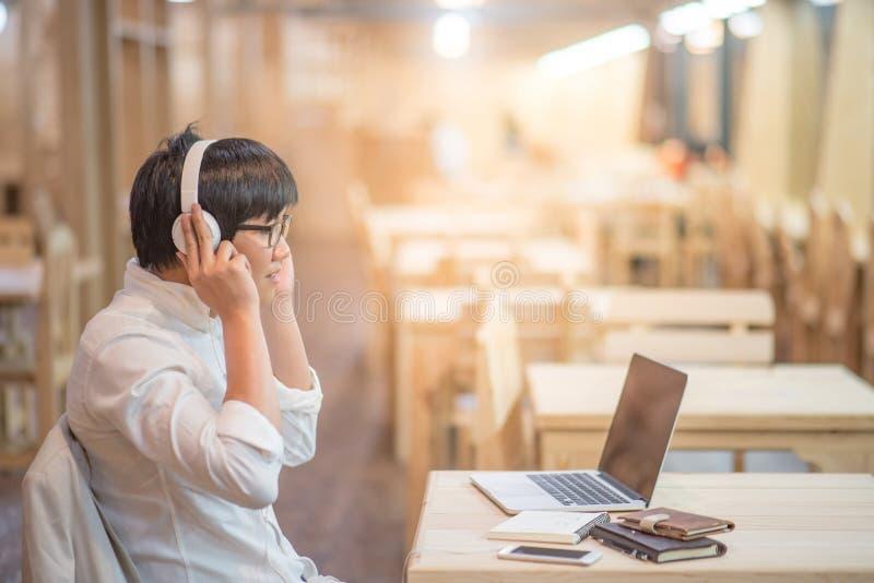 Asiatischer junger Mann mit Kopfhörern hörend Musik stockfoto