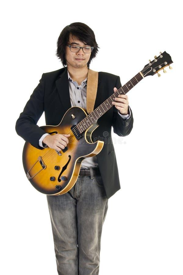 Asiatischer junger Musiker, der Gitarre spielt stockbilder