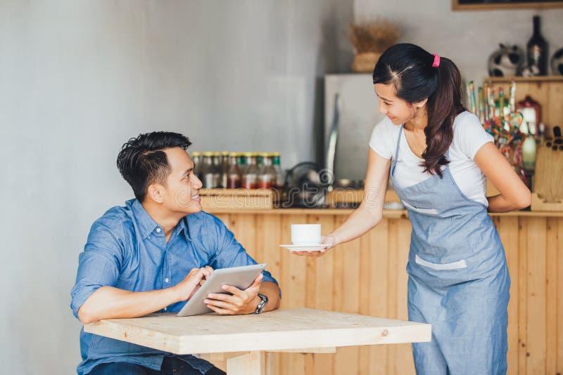 Asiatischer Kellnerinumhüllungskaffee stockbild