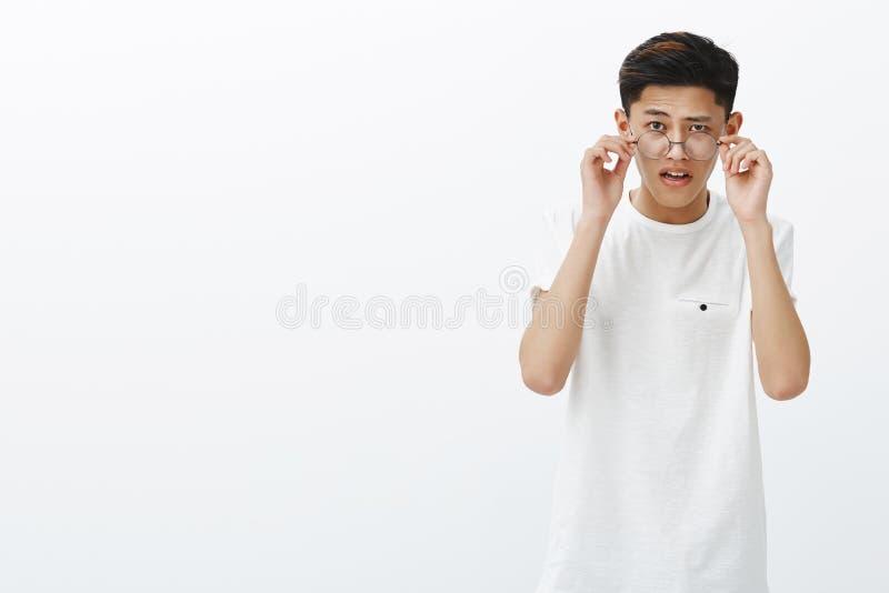 Asiatischer Kerl, der Gläser als seiend zweifelhaft entfernt, merkwürdige Sache sehend, überraschter und überraschter offener Mun stockfotografie