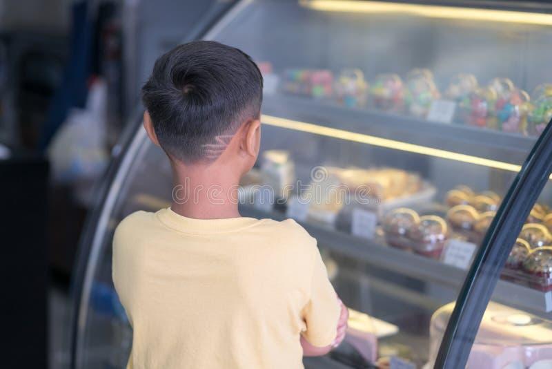 Asiatischer Kinderjunge, der am Bäckereigeschäft wartet und Bäckerei die er beschließt zu mögen stockfotos