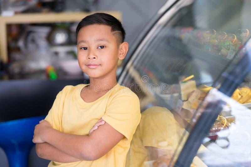 Asiatischer Kinderjunge, der am B?ckereigesch?ft wartet und B?ckerei die er beschlie?t zu m?gen lizenzfreie stockfotos