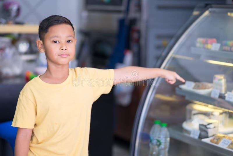Asiatischer Kinderjunge, der am B?ckereigesch?ft wartet und B?ckerei die er beschlie?t zu m?gen lizenzfreies stockbild