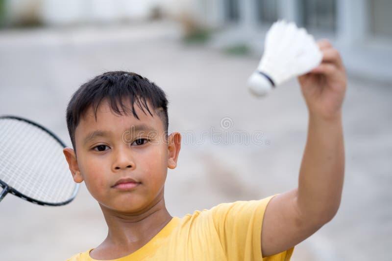 Asiatischer Kinderjunge, der zu Hause Badminton spielt stockfotografie
