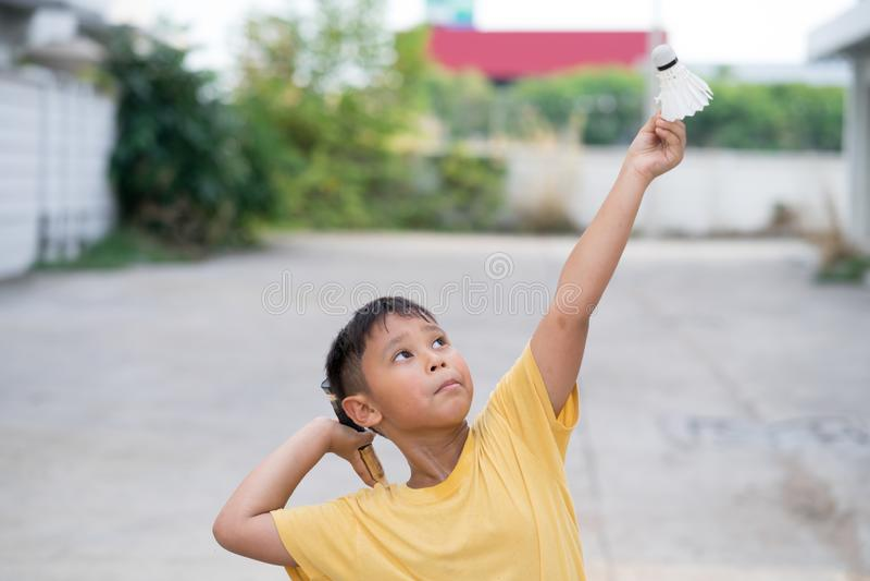 Asiatischer Kinderjunge, der zu Hause Badminton spielt stockfotos
