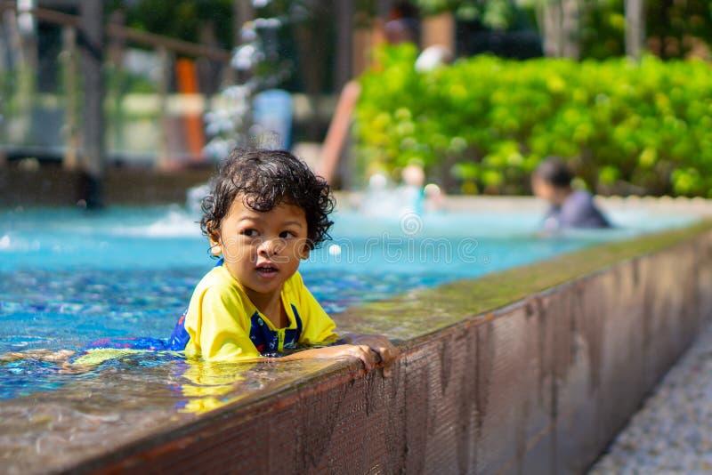 Asiatischer Kinderjunge lernen Schwimmen in einem Swimmingpool stockbild