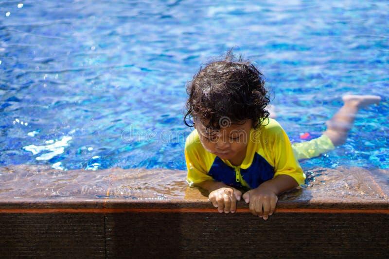 Asiatischer Kinderjunge lernen Schwimmen in einem Swimmingpool stockbilder