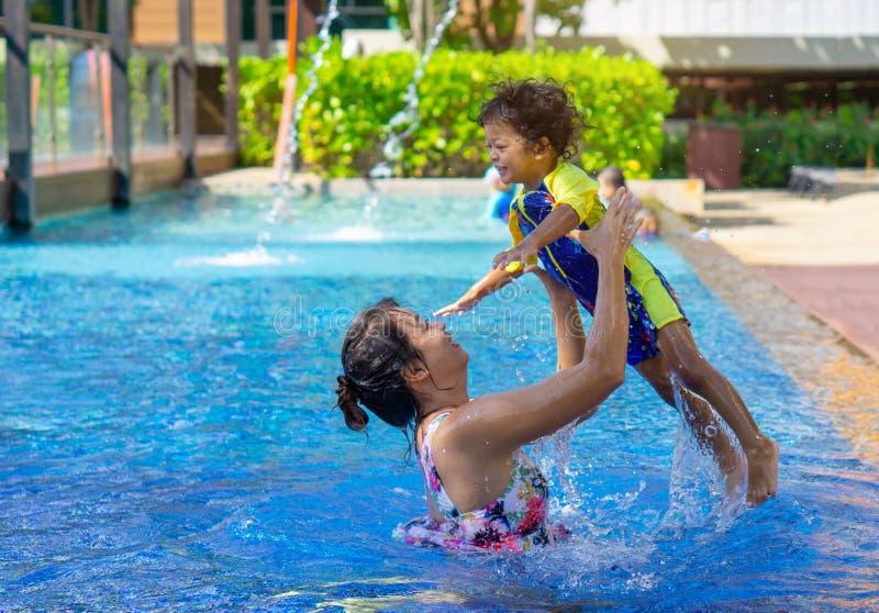 Asiatischer Kinderjunge lernen Schwimmen in einem Swimmingpool mit Mutter - SU stockfotos