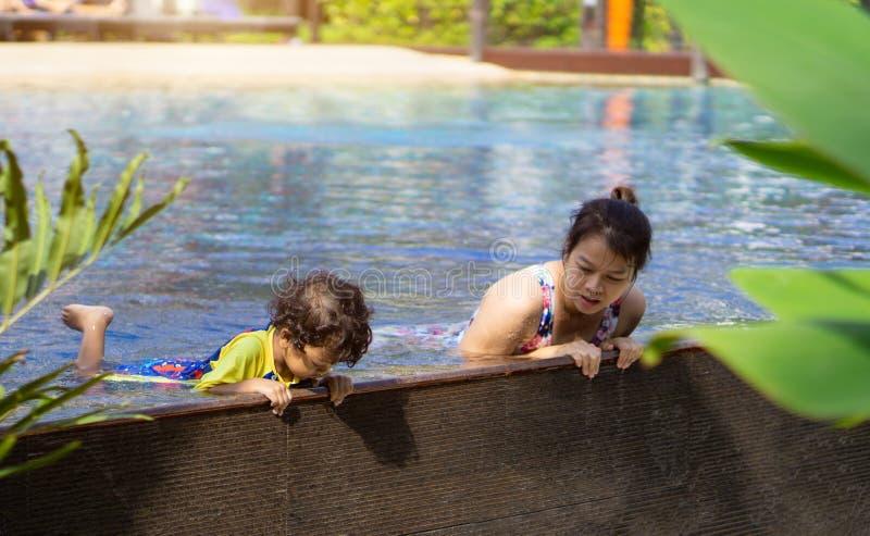 Asiatischer Kinderjunge lernen Schwimmen in einem Swimmingpool mit Mutter - SU stockbild