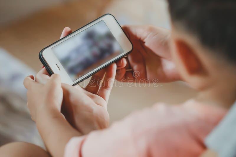 Asiatischer Kinderjungenholding- und -touch Screen von Smartphone lizenzfreies stockbild