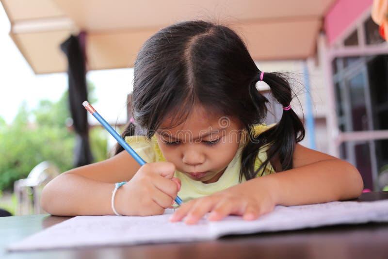Asiatischer Kindermädchen-Gebrauch Bleistift schreiben Briefe auf dem Buch lizenzfreie stockbilder