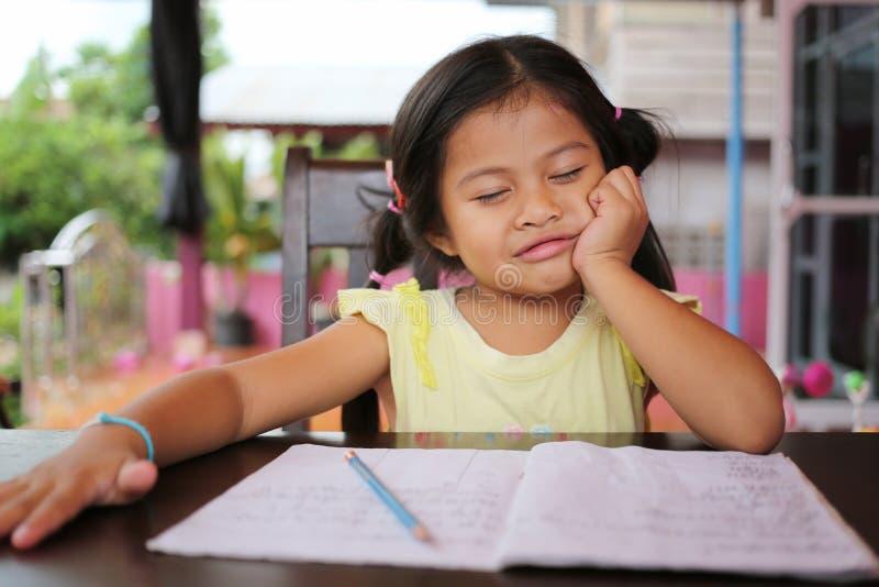 Asiatischer Kindermädchen-Gebrauch Bleistift schreiben Briefe auf dem Buch lizenzfreies stockfoto