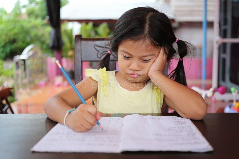 Asiatischer Kindermädchen-Gebrauch Bleistift schreiben Briefe auf dem Buch lizenzfreies stockbild