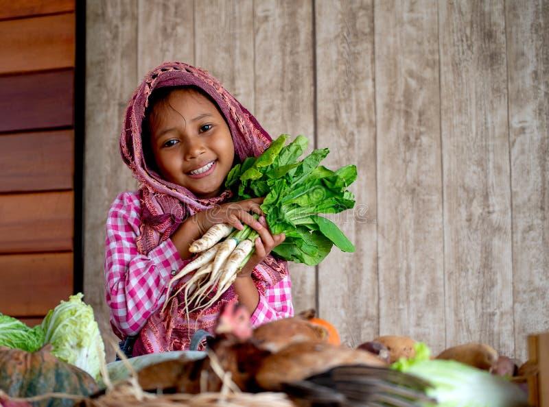 Asiatischer kleiner Blick des jungen Mädchens vorwärts und Lächeln unter verschiedenen Arten des Gemüses hält auch den Rettich hi stockbilder