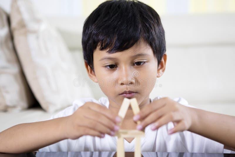 Asiatischer kleiner Junge, der ein Haus errichtet stockbild