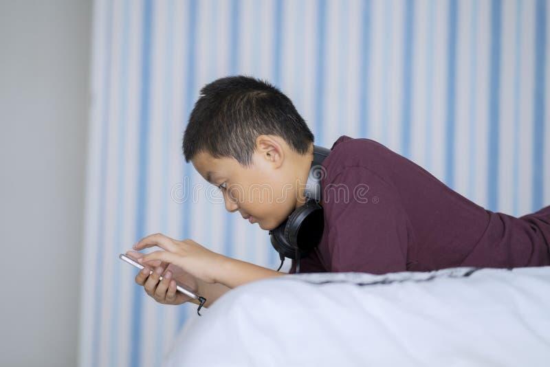 Asiatischer kleiner Junge, der einen Smartphone verwendet lizenzfreies stockbild