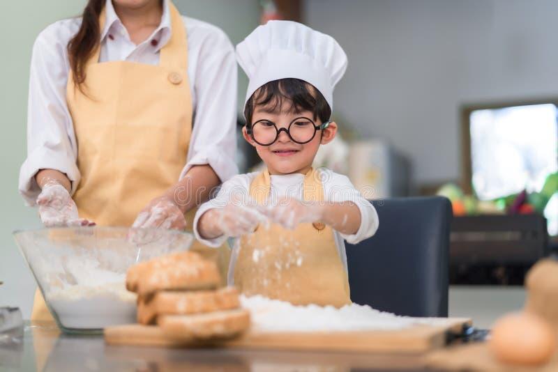 Asiatischer kleiner Junge des Patissiers, der Bäckereibrotplätzchen und -kuchen köstliche süße Nahrung macht lizenzfreies stockfoto