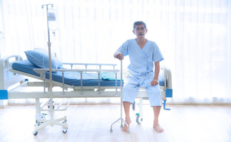 Asiatischer kranker oder älterer alter Mann, der allein auf dem Bett des Patienten sitzt stockfotografie