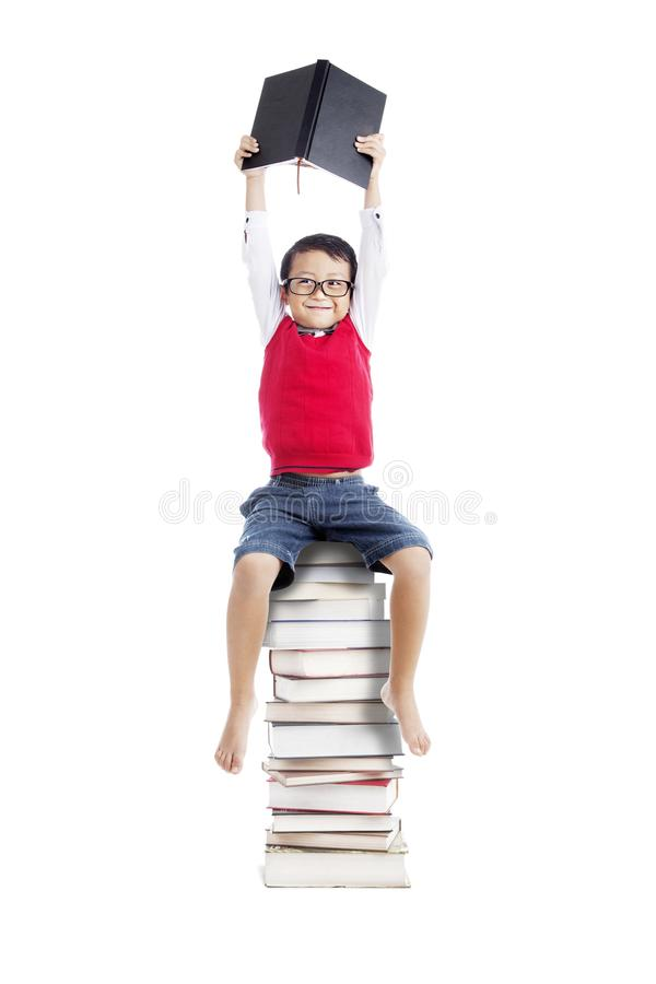 Asiatischer Kursteilnehmer, der auf Stapel Büchern sitzt stockfotografie