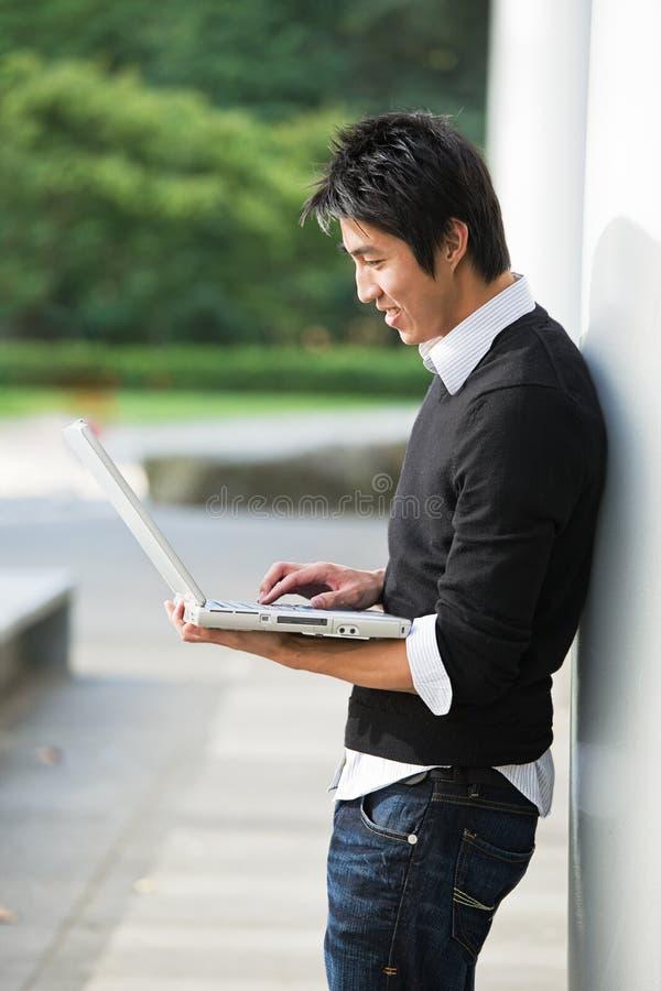 Asiatischer Kursteilnehmer und Laptop stockfotos