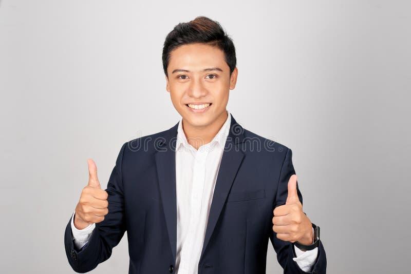 Asiatischer lächelnder Geschäftsmannvertretungsdaumen herauf beide Hand, lokalisiert auf weißem Hintergrund lizenzfreies stockbild