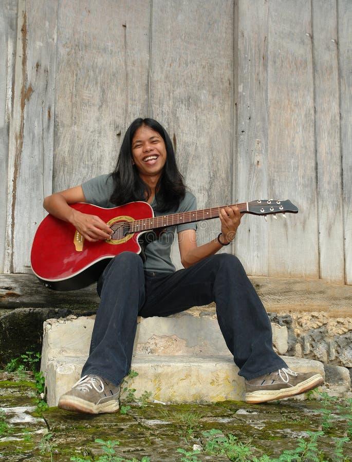 Asiatischer langhaariger Junge, der Gitarre. spielt lizenzfreie stockfotos
