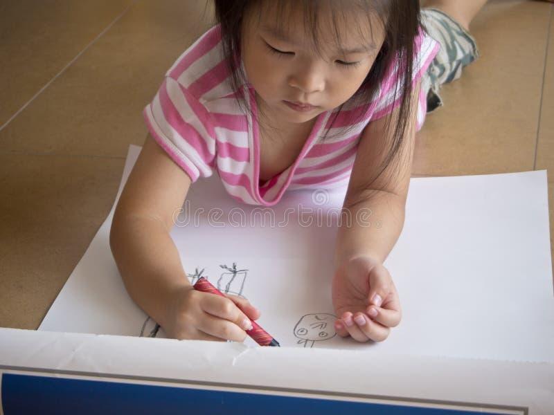 Asiatischer Mädchen Malereizeichenstift auf großen Blättern Papier auf dem Boden stockfotografie