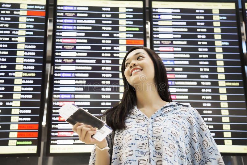 Asiatischer Mädchenprüfungsflug am Flughafen lizenzfreie stockbilder