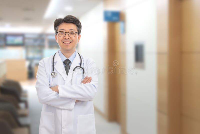 Asiatischer männlicher Doktor, der im Hintergrund des Krankenhauses lächelt stockfotos