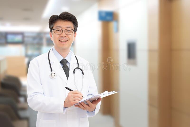 Asiatischer männlicher Doktor, der im Hintergrund des Krankenhauses lächelt stockbilder