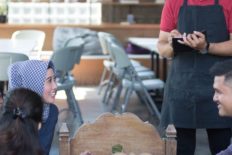 Asiatischer männlicher Kellner schreiben Aufträge von den costumers am Café in Hintergrund stockbilder