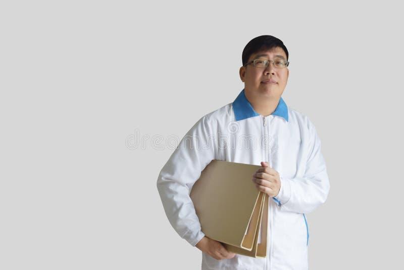 Asiatischer Mann alterte 40 zur weißen Uniform des langärmligen Hemds und hielt eine braune Datei auf Hintergrund des Graus mit B lizenzfreie stockbilder