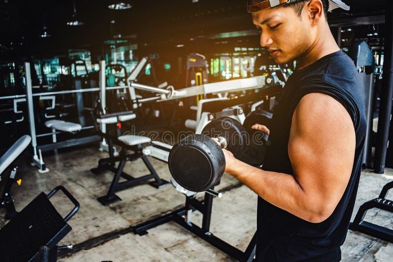 Asiatischer Mann Bodybuilder mit Dummkopf belastet Energie h?bsches athle stockfotografie