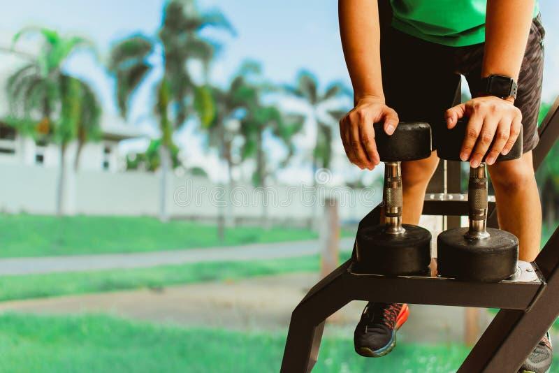 Asiatischer Mann Bodybuilder mit Dummkopfgewichten treiben hübsche athletische Übungen an Metapher-Eignung und Trainingskonzeptüb lizenzfreies stockfoto