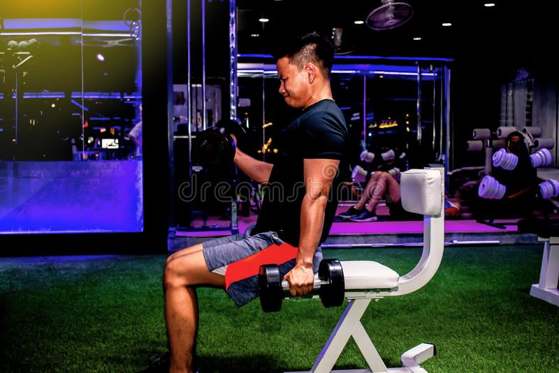Asiatischer Mann Bodybuilder mit hübschem athletischem der Dummkopfgewichts-Energie lizenzfreie stockfotografie