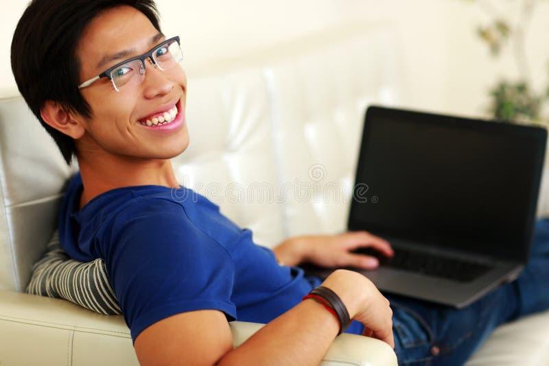 Asiatischer Mann, der auf dem Sofa mit Laptop liegt lizenzfreie stockfotos
