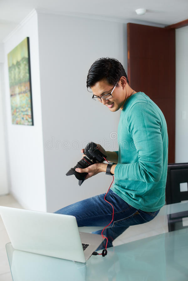 Asiatischer Mann, der DSLR zum Laptop PC Downloading-Foto begrenzt stockbild
