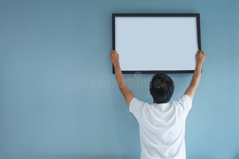 Asiatischer Mann, der einen Bilderrahmen auf blauer Wand hält lizenzfreies stockbild